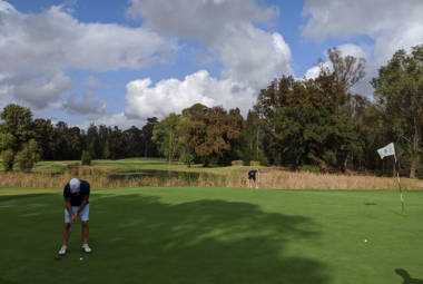 Putting out on the green with the flag in the hole